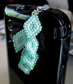 """This cute beaded dust plug is hand beaded and attached to a clear dust plug to coordinate with any color phone!   Beaded with green and white Delica beads it is a great cell phone accessory for anyone! The phone charm hangs approx 1.75"""" (4.44 cm) and is approx .75"""" (1.9 cm) in width."""