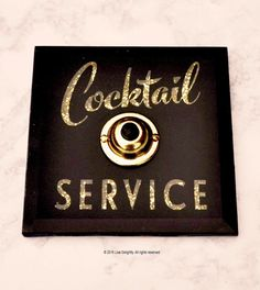 The perfect gift for anyone who appreciates a little cocktail service on occassion ( and who doesnt? ) I have always had a love affair with antique glass signage found in old bars and hotels. This COCKTAIL SERVICE button celebrates such signage from a bygone era. Reverse printed beveled glass has a shadow box effect with a gold glitter background. This piece not only rings but lights from within when the antiqued brass button is pressed. Our buttons have been featured in Veranda, Elle…
