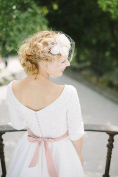 noni 2014 grace, hochzeitskleid mit v ruecken, rosa schleifenband in der taille und langen aermeln mit manschetten, birdcage mit rosen in elfenbein (Foto: Le Hai Linh) (http://www.noni-mode.de)