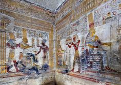 """'Isis Shrine in Seti I Temple at Abydos.'  The Isis Shrine is one of three small sanctuaries that are located north of the Inner Osiris Hall in the Seti I Temple at Abydos. The relief on the left (on the northern wall of the shrine) depicts an enthroned Isis, holding a sistrum and a """"menat"""" necklace in her right hand. With her other hand she presents to Seti a staff from which hang suspended symbols for his jubilees. Behind Isis stands Horus in an protective posture."""