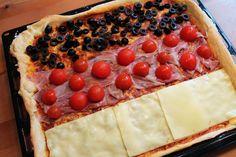 Eine Pizza mit schwarzen Oliven oben, roten Kirschtomaten und Schinken in der Mitte und gelbgoldenem Käse unten