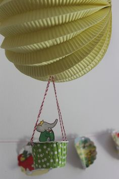 I purchased a damaged book from Amazon and cut it up for decorations. Shown here in the garland as well as a hot air balloon passenger. (made with a paper lantern, twine, and a cupcake liner) Babar Party