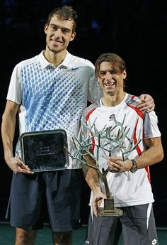 Spain's David Ferrer, right, holds the winner's trophy after winning the final of the Paris Tennis Masters tournament against Jerzy Janowicz of Poland, left, Sunday Nov. 4, 2012.(AP Photo/Remy de la Mauviniere)