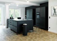 reforma cocina con isla central para fregadero, muebles color carbón y pared pintada de negro, suelo parquet