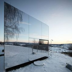 The mirrored surfaces of this modular housing unit help it to blend in with the surrounding countryside