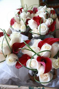 Bouquets of white roses, magenta mini calla lilies and bear grass loops