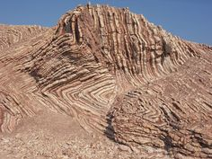 Oman. metamorphic rock that has been bent and folded in a number of different ways while being subducted on the ocean floor. However this subduction process stopped and the rock was brought to the surface and the formation is the red and white rock you can see in the picture.