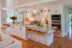 Dreamy! Kitchen with white cabinets, large kitchen island, barstools, glass pendants over island and beadboard ceiling. Polhemus Savery DaSilva.
