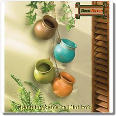 Dangling Santa Fe Mini Pots - Straight from the kitchen of a Santa Fe gourmet, this darling decoration recalls the fabled cooking pots treasured for generations in the Southwest. Four graceful earthtone vessels with jute hanging loops ready to brighten any corner!