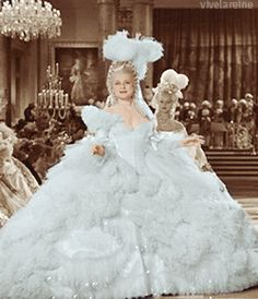 "MGM's Marie Antoinette was intended to be filmed in color. Adrian spared no expense in choosing the most extravagant of fabrics, colors & designs for his pieces - much to the ire of the MGM heads who balked at the increasingly high production cost for the film. When Sidney Franklin was replaced as director by W.S. Van Dyke, the decision was made to cut the plans for technicolor and film Marie Antoinette in black and white to curb the already bloated budget for the film."" Here, a colorized…"