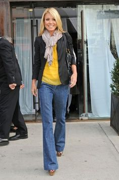 Kelly Ripa wearing bootleg jeans, bright yellow top, tan scarf