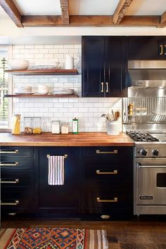 BLACK CUPBOARDS, BUTCHER BLOCK COUNTER, WHITE SUBWAY TILE BACKSPLASH, BRASS HARDWARE, OPEN SHELVING, WOOD BEAMS Blair Harris Interior Design (via Grey and Scout)