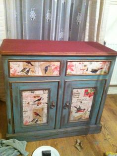 old sideboard , updated with annie sloan chalk paint in province and primer red , decoupged doors with rossi gift wrap . Waxed with annie sloan clear wax .~ sorry no source