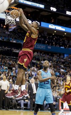Cleveland Cavaliers forward LeBron James, left, dunks as Charlotte Hornets guard Kemba Walker looks on in the second half of an NBA basketball game Friday, Nov. 27, 2015 in Charlotte, N.C. (AP Photo/Nell Redmond)