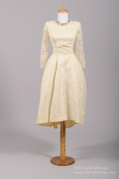 Designed in the 60's, by Lorrie Deb, this beautiful asymmetrical vintage wedding dress is done in an ecru floral lace over an acetate lining of the same colo...