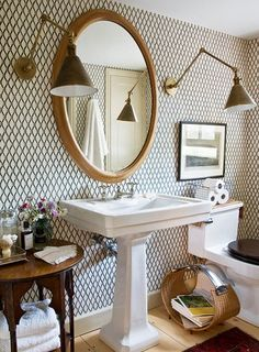 wallpaper in bathroom, gold oval mirror, wall sconces, pedestal sink