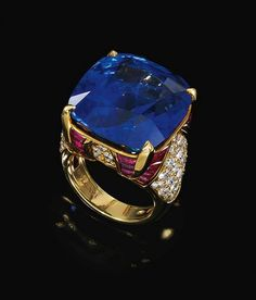 SAPPHIRE, RUBY AND DIAMOND RING, BULGARI Centering on a cushion-shaped sapphire to a mount enhanced with buff-top rubies and brilliant-cut diamonds