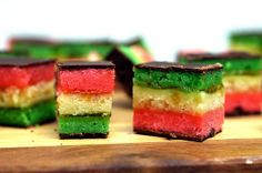 ItAlian marzipan SEVEN LAYER COOKIES: 4 large eggs, separated  1 cup sugar  1 (8-oz) can almond paste  2 1/2 sticks (1 1/4 cups) unsalted butter, softened  1 teaspoon almond extract  2 cups all-purpose flour  1/2 teaspoon salt  25 drops red food coloring  25 drops green food coloring  1 (12-oz) jar apricot preserves, heated and strained  7 oz fine-quality bittersweet chocolate (not unsweetened), chopped