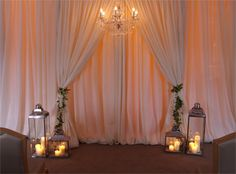 Ivory double ceremony backdrop with wisteria tie backs, glass baroque chandelier, large and medium coach lanterns with pillar candle clusters, and LED uplighters in amber by www.stressfreehire.com #venuetransformers