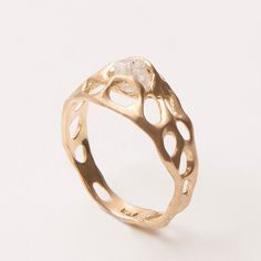 A handmade 14k yellow gold ring set with a beautiful raw uncut diamond or other raw gem .    Unlike most raw diamonds that are used in jewelry the