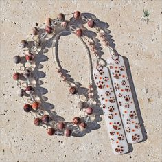 Hand-painted paw prints on this Mexican Laguna Agate chime. Hanging patio decor, 28 inches long.