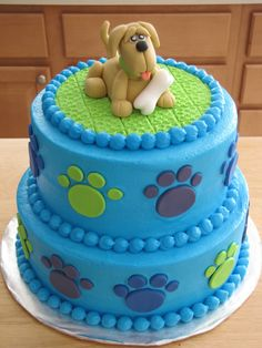 Buttercream covered cake with fondant puppy topper and paws.