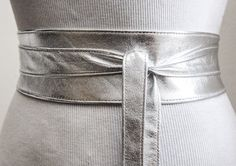 Silver leather obi belt is made from real leather This beautiful belt will accentuate your style be it casual or formal. Cinch in your waist and get instant curves and a flatter tummy  Main color: Silver  Material: Foil metallic leather Width: 3, 4, 5 and 6 inches 3 inches is featured in the pictures   SIZE SMALL to fit waist sizes (in inches) 20 to 28 inches CLOTHING SIZE UK 4 to 10 US 0 to 6 total length 70 inches  MEDIUM to fit waist sizes (in inches) 28 to 36 inches CLOTHING SIZE UK 10…