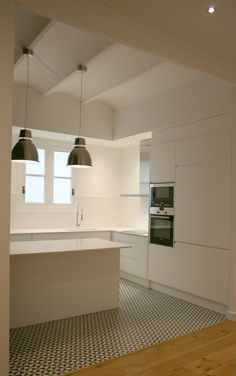 Patterned tiled floor in the kitchen accentuated by a plain neutral colour on the cabinets