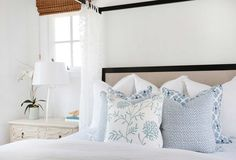 Curtains around bed.Layered throw pillows in different patterns but similar shades of blue create subtle interest in this calm, coastal-style bedroom. The beautiful blue pillows pop against the crisp white bed linens. Coastal Master Bedroom, Coastal Bedrooms, Coastal Living Rooms, Bedroom Decor, Coastal Curtains, Beach Bedrooms, Coastal Bedding, White Bedding, Guest Bedrooms