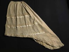 """1882-83 Skirt. Museum of London. This skirt is part of a dress that is included in Janet Arnold's 'Patterns of Fashion: Englishwomen's dresses and their construction c. 1860-1940' (pages 36-37). Arnold describes it as 'a dinner dress in ivory silk with satin stripes 3/8"""" wide, 1/16"""" apart. It is trimmed with ivory embroidered net and lace."""