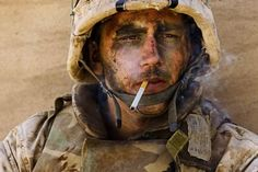 American soldier with burnt face smoking a cigarette in Iraq.