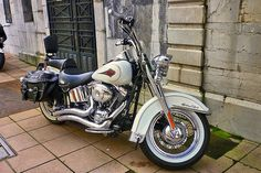 White Harley Davidson motorcycle with black leather saddle bags, chrome pipes, spoke wheels, & white wall tires. ~ Sharp!