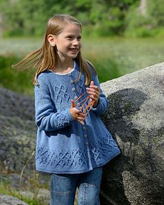 Thigh length cardigan with empire waist and gathered skirt. Cables accent the bodice, cuffs and hem and a row of buttons fastens the front. (children 4-10 years)