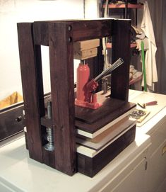 Here's my recently finished press I built from a bunch of lumber, some angle-iron and a car jack. Total cost about $60, though I splurged on stain, melamine iron-on-edging, and all new materials even though I could find most of the same stuff in the garbage and in my dad's garage and might have saved myself about $40.   Now my laundry area is good for getting clothes dirty, as well as getting them clean.