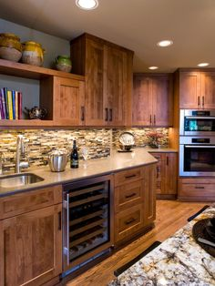 Mosaic tiles in a mix of earthy tones bring beautiful texture and dimension to the backsplash of this traditional kitchen. The dark brown wood of the cabinets is the perfect foil.