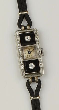 An Art Deco diamond and onyx cocktail watch  The small square dial with black Arabic numerals, set between two rectangular onyx panels, each centred with an old-cut diamond, the rectangular watch head bordered to each side by a line of small single-cut diamonds, the movement signed Longines, outer case stamped 'platine', on later black cordette strap, watch head length 2.8cm.