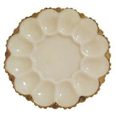 Vintage scalloped glass egg plate with gold trim. Made by Anchor Hocking.   Product: Egg plateConstruction Material: GlassColor: Milk and goldFeatures: Scalloped edgesDimensions: 1.75 H x 10 DiameterNote: Due to the vintage nature of this product, some wear and tear is to be expected. Products may show signs of brand marks, scrapes or other blemishes.Cleaning and Care: Hand wash