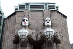 The huge, lamp-holding statues at the entrance of Helsinki Central railway station are now wearing Kiss face masks which were painted by four local fans.