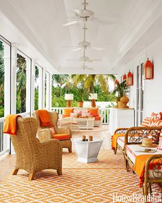 Verandah in fresh white and orange tones. Ceiling fans and cane furniture give it a summery look.