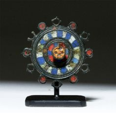 Roman Enameled Bronze Brooch, From Gaul or Britain, 2nd-3rd Century ADThis is a bronze enameled brooch in the shape of a wheel with a blue and white checkered pattern around a raised circle decorated with bright orange. Small plate brooches in...