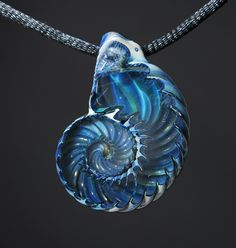 The Ammonite pendants are multiple layers of glass that are cut and polished on one side using lapidary techniques (stone cutting) to expose