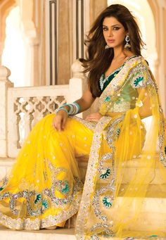 Yellow net stone and resham embroidered saree. As shown contrasting green velvet blouse can be made available and also can be customized upto 42 inches due to fabric limitation. (Slight variation in color is possible.) data-pin-do=
