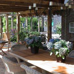 Heerlijk zonnige plaatje van een mooie overkapping in je tuin!