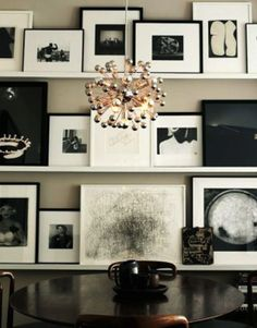 art wall with ledges (good for changing up more often). those predominantly Again another 'overdone' display...they seem to go so overboard for architectural digest and what not....  black photos help achor what would have been too much white, in my opinion.