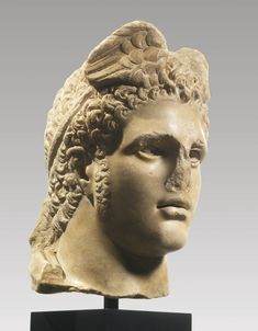 A Monumental Marble Head of Hermes-Thoth, Late Hellenistic, circa 2nd Century B.C., probably from a standing cult figure of the god wearing a chlamys, his powerful face with strong chin, parted lips, & deep-set almond-shaped eyes originally inlaid with sheet bronze for the eyelashes, marble for the whites of the eyes, & glass or colored stone for the irises & pupils, his hair swept up above the forehead, arranged in rows of short overlapping curls, & bound in a diadem...Height 17 in.