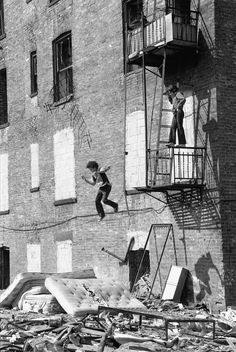 A boy jumping onto a mattress from a fire escape in the Lower East Side, c. Photo credit: Martha Cooper — in New York, New York. Hip Hop, Vintage Photography, Street Photography, Urban Photography, People Photography, Martha Cooper, Old Photos, Vintage Photos, Fosse Commune