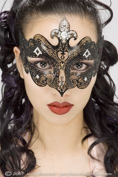 This is exquisite.  I think it's laser cut foil or something, that's then glued to the face.  You could probably find and adapt something from a craft store.  (I have seen similar things done with lace).