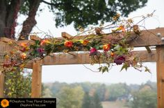 Swag of simple branches, greenery, flowers over gazebo door.