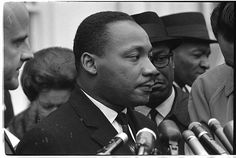 [Martin Luther King, Jr., head-and-shoulders portrait, facing right, at microphones, after? meeting with President Johnson to discuss civil rights, at the White House, 1963]