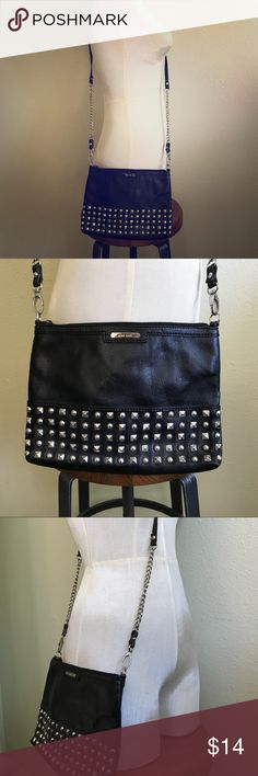 Nine West Studded Crossbody Bag with Chain Strap This barely used, like-new crossbody bag is a statement in and of itself! The supple black faux leather goes with everything, while the rows of studs and chain strap give this utilitarian bag quite a rocker edge! Nice, flat profile doesn't cause a big pooch on your side. You can even flip it around and use the all-black side for more versatility. Includes an inner zippered compartment and working clips to release the strap and use as a clutch…